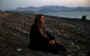 REUTERS / Yannis Behrakis: De blinde Amoun (70) uit Aleppo rust uit op het strand van Kos na haar overtocht in een rubberboot met veertig anderen vanuit Turkije